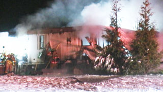 Firefighters battle freezing conditions as flames destroy mobile home